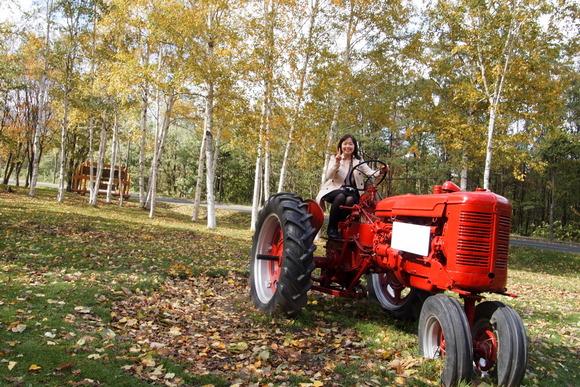 赤いトラクターにまたがり記念撮影
