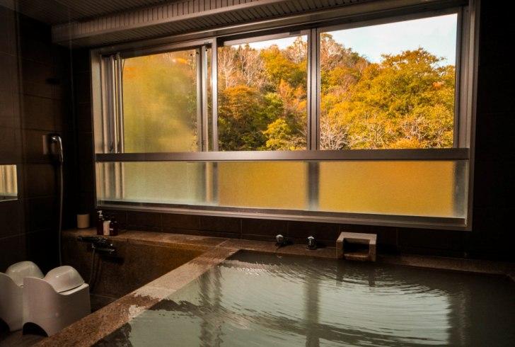 客室展望風呂と窓の外に広がる紅葉