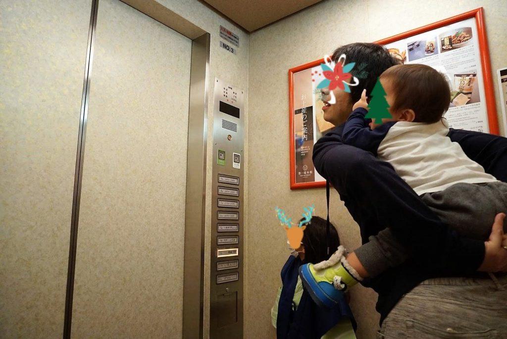 エレベーターの中で息子をおんぶするパパと娘の画
