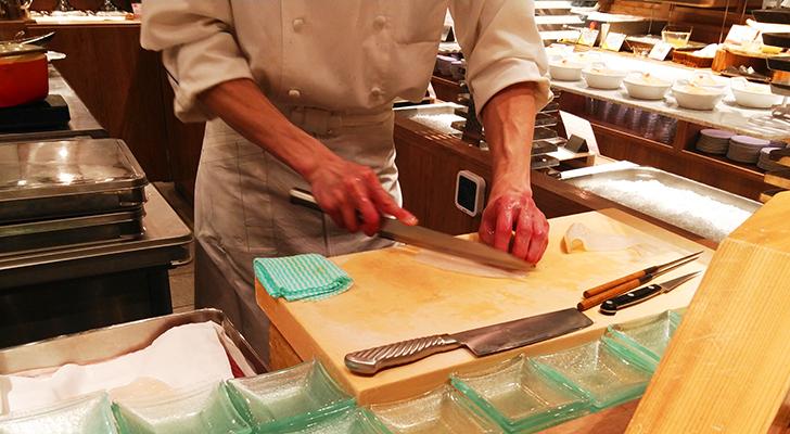 イカを包丁でさばく料理人