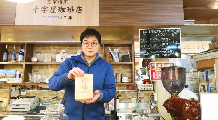 お土産に購入した挽きたて珈琲豆を差し出す菅原さん