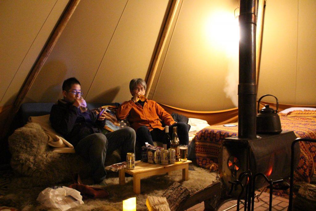 薪ストーブ前のソファを陣取ってお酒を酌み交わす二人