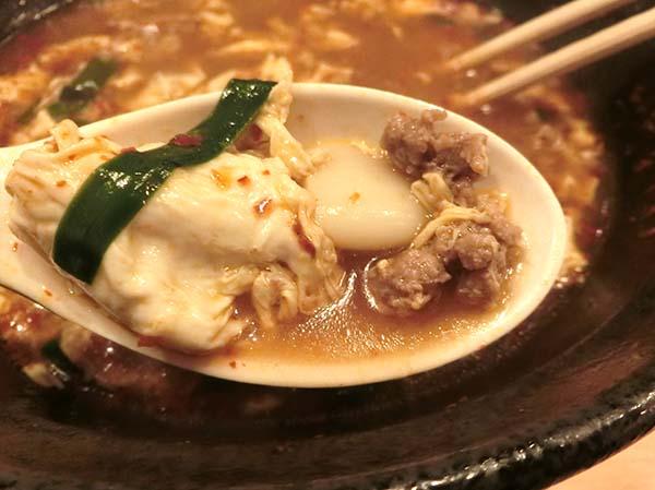 レンゲですくったニラ・ニンニク・ひき肉・溶き卵
