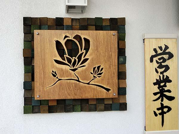 木彫りの木蓮が印象的なお店の看板
