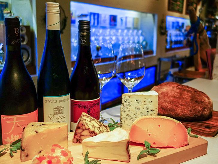 ワインボトルと多彩なチーズが並ぶワインバーフェルマータの店内