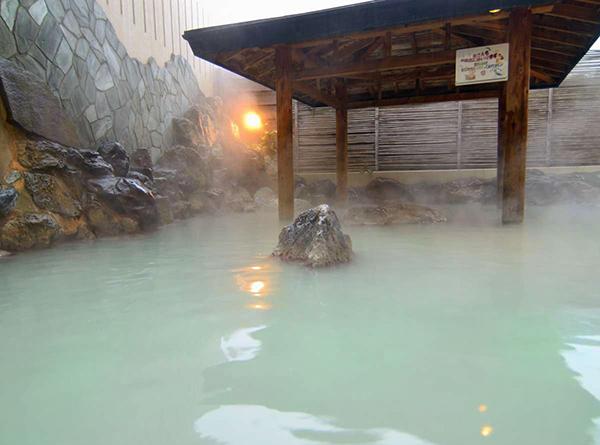 東屋のある岩に囲まれた露天風呂