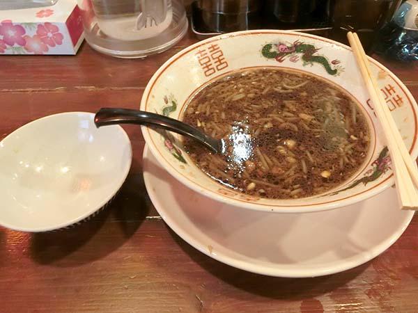 食べ終わった丼とお茶碗。赤茶色の濃いスープが残っている