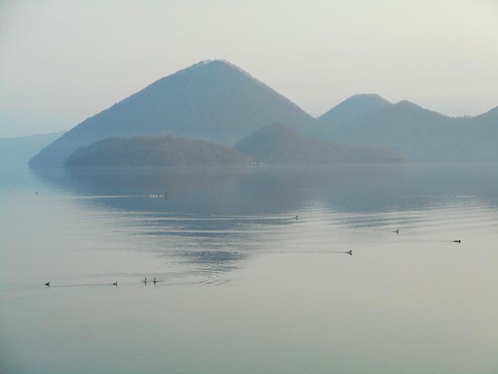 朝靄のかかる洞爺湖と中島。洞爺湖の水音と水鳥の羽音が、静けさを一層強く感じさせます。